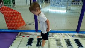4k μήκος σε πόδηα του ευτυχούς εύθυμου άλματος αγοριών μικρών παιδιών και του παιχνιδιού με το μεγάλο πιάνο στο πάτωμα στο λούνα  απόθεμα βίντεο