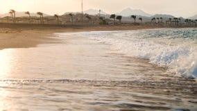 4k μήκος σε πόδηα του καταπληκτικού ηλιοβασιλέματος πέρα από τα κυλώντας κύματα θάλασσας στην αμμώδη παραλία απόθεμα βίντεο
