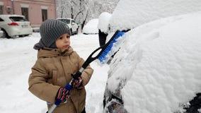 4k μήκος σε πόδηα του μικρού παιδιού που βοηθά το καθαρίζοντας αυτοκίνητο πατέρων του από το χιόνι με τη βούρτσα απόθεμα βίντεο