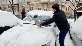4k μήκος σε πόδηα του νεαρού άνδρα που αφαιρεί το χιόνι από το αυτοκίνητό του στο πρωί πρίν οδηγά στην εργασία φιλμ μικρού μήκους