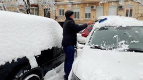 4k μήκος σε πόδηα του νεαρού άνδρα που αφαιρεί το χιόνι από το αυτοκίνητό του στο πρωί πρίν οδηγά στην εργασία απόθεμα βίντεο