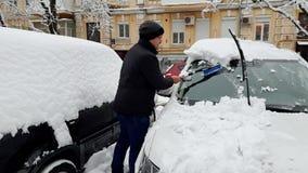4k μήκος σε πόδηα του νεαρού άνδρα που καθαρίζει το αυτοκίνητό του από το χιόνι μετά από τη χιονοθύελλα με την τηλεσκοπική βούρτσ απόθεμα βίντεο