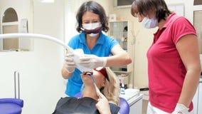 4k μήκος σε πόδηα του οδοντιάτρου που ρυθμίζει και που ανοίγει το λαμπτήρα για τη λεύκανση δοντιών απόθεμα βίντεο