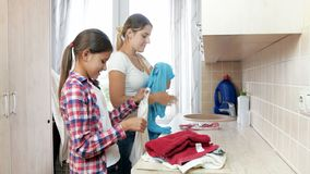 4k μήκος σε πόδηα του όμορφου χαμογελώντας κοριτσιού που βοηθά τη μητέρα της που κάνει τα οικιακά στο πλυντήριο απόθεμα βίντεο