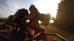 4K μήκος σε πόδηα: γιος με την οδήγηση πατέρων από την μπροστινή άποψη καμερών quadrocycle φιλμ μικρού μήκους