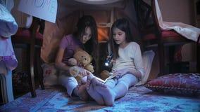 4k μήκος σε πόδηα δύο αδελφών που διαβάζουν το βιβλίο τη νύχτα με το φακό απόθεμα βίντεο