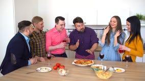 4K μεγάλη ομάδα ευτυχών νέων φίλων που τρώνε τη take-$l*away πίτσα στο σπίτι απόθεμα βίντεο