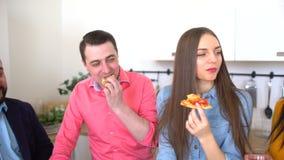 4K μεγάλη ομάδα ευτυχών νέων φίλων που τρώνε τη take-$l*away πίτσα στο σπίτι Ομάδα φίλων που απολαμβάνουν το κόμμα γευμάτων στο σ απόθεμα βίντεο