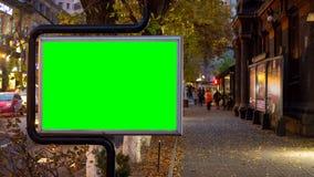 4K βίντεο χρονικού σφάλματος Μεγάλος πίνακας διαφημίσεων με την πράσινη οθόνη στα πλαίσια των περπατώντας θολωμένων ανθρώπων στην απόθεμα βίντεο