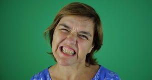 4k - Μια γυναίκα brunette που ένας κακός μορφασμός, που παρουσιάζει τα δόντια και χαμόγελα απόθεμα βίντεο