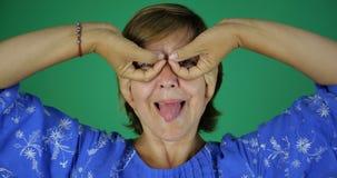 4k - Μια ενήλικη γυναίκα παρουσιάζει γλώσσα της με ένα χαμόγελο και κάνει μια χειρονομία των δάχτυλων στοκ εικόνες