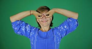 4k - Μια ενήλικη γυναίκα που χαμογελά και που κάνει μια χειρονομία των δάχτυλων στη μορφή στοκ εικόνα