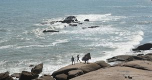 4k οι άνθρωποι βλέπουν στη λαμπιρίζοντας ωκεάνια θάλασσα τα ευμετάβλητα κύματα βρυχηθμού στους βράχους παράκτια ακτή απόθεμα βίντεο