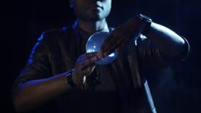4K ο μάγος κρατά τη σφαίρα μεταξύ των αντίχειρών του και της στροφής του που παρουσιάζει ελαφρύ παιχνίδι απόθεμα βίντεο