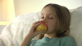 4K παιδί που τρώει τα μήλα προσέχοντας τη TV, χαλάρωση κοριτσιών στον καναπέ, λεωφορείο στη διαβίωση απόθεμα βίντεο
