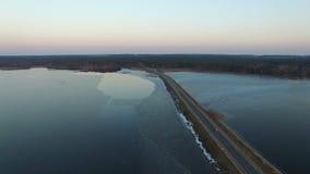 4K Πτήση πέρα από το δρόμο στο νερό την πρώιμη άνοιξη στο ηλιοβασίλεμα, εναέριο απόθεμα βίντεο