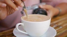 4K σε αργή κίνηση χέρι της γυναίκας που χρησιμοποιεί το κουτάλι για να αναμίξει τον καφέ στο φλυτζάνι απόθεμα βίντεο