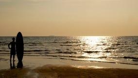 4K σκιαγραφία της στάσης ατόμων surfer στην παραλία θάλασσας με τους μακριούς πίνακες κυματωγών στο ηλιοβασίλεμα στην τροπική παρ απόθεμα βίντεο