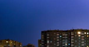 4k συνδετήρας χρονικού σφάλματος της θύελλας νύχτας με την αστραπή κάτω από τα multi-storey κτήρια Φως στα παράθυρα των σπιτιών απόθεμα βίντεο