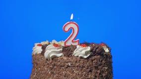 4k - Τον αριθμό δύο κερί γενεθλίων σε ένα εύγευστο κέικ σοκολάτας, μπλε οθόνη απόθεμα βίντεο