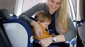 4k το μήκος σε πόδηα της γυναίκας που βάζει το παιδί της μέσα το κάθισμα ασφάλειας αυτοκινήτων Ασφάλεια και προστασία στις μεταφο απόθεμα βίντεο