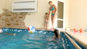 4k το μήκος σε πόδηα της ευτυχούς νέας μητέρας με iun η δημόσια πισίνα Οικογενειακή απόλαυση κολυμπώντας και παίζοντας με το νερό απόθεμα βίντεο