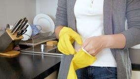 4k το μήκος σε πόδηα της νέας νοικοκυράς που φορά το κίτρινο λατέξ φορά γάντια κάνοντας τα οικιακά απόθεμα βίντεο