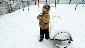 4k το μήκος σε πόδηα του εύθυμου μικρού παιδιού απολαμβάνει και παίζοντας με το χιόνι στο χειμερινό πάρκο φιλμ μικρού μήκους