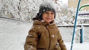 4k το μήκος σε πόδηα του εύθυμου μικρού παιδιού απολαμβάνει και παίζοντας με το χιόνι στο χειμερινό πάρκο απόθεμα βίντεο