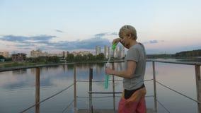 4k - Το μοντέρνο άτομο απολαμβάνει με τις φυσαλίδες σαπουνιών στη γέφυρα απόθεμα βίντεο