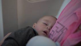 4k - χαριτωμένοι ύπνοι λίγων μωρών σε ετοιμότητα της μητέρας του κατά τη διάρκεια της πτήσης αεροπλάνων απόθεμα βίντεο
