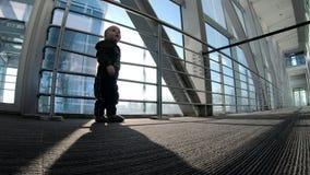 4k - Χαριτωμένο μικρό παιδί που περιμένει το αεροπλάνο του στο airtrap στο φως του ήλιου απόθεμα βίντεο