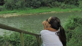 4k όμορφη συνεδρίαση κοριτσιών στα σκαλοπάτια βράχου μέσα βαθιά - πράσινο δάσος κοντά στον ποταμό βουνών που με το καθαρό αέρα κα απόθεμα βίντεο