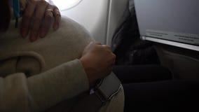 4k, азиатская беременная женщина касаясь ее tummy внутри самолета Отключение полета акции видеоматериалы