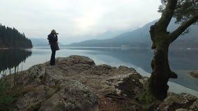 4K Девушка делает фото изумлять озеро Bohinj, панорамный взгляд Джулиан Альпы, национальный парк Triglav, Словения, Европа зима в видеоматериал