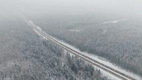 4K Дорога в лесе зимы с управлять автомобилями на снежностях воздушный панорамный взгляд Исчезая перспектива видеоматериал
