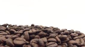 4k зажарило в духовке кофейные зерна вращает на черной предпосылке Ингредиент для кофе видеоматериал