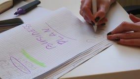 крупный план 4K Коммерсантка пишет заголовок для ее бизнес-плана Руки красивых женщин пишут в тетради сток-видео
