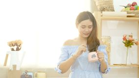 4K красивая азиатская женщина наслаждается выпить кофе в утре с smiley стороной около окна с солнечным светом утра акции видеоматериалы