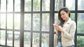 4K красивая азиатская молодая куртка костюма носки бизнес-леди используя применение на болтовне умного телефона отправляя СМС с д акции видеоматериалы