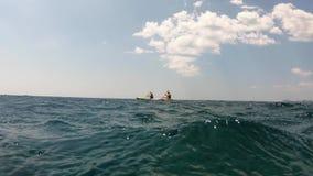 4K 2 люд полоща в каяке или каноэ в Адриатическом море Взгляд от воды видеоматериал