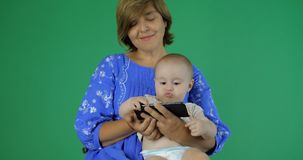 4k - Мама и младенец наблюдают что-то смешное на ее смартфоне сток-видео