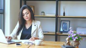 4K отснятый видеоматериал, занятая бизнес-леди работая с ноутбуком, писать на книге и думая с серьезной стороной на месте для раб видеоматериал