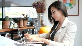 4K отснятый видеоматериал, занятая бизнес-леди работая с портативным компьютером и думая с серьезной стороной в кафе кофейни в го акции видеоматериалы