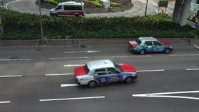 4K повысило взгляд над занятой дорогой с красными автомобилями и автобусом такси в Гонконге акции видеоматериалы