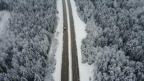 4K Полет над дорогой в замороженном лесе зимы с управлять автомобилями воздушный панорамный взгляд Исчезая перспектива акции видеоматериалы