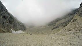 4K Промежуток времени в горах с переменчивой погодой: солнце и глубокие облака Люди идущ и пеший вокруг Словения сток-видео