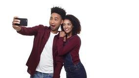 4k - 做selfie和观看做的照片的愉快的快乐的美国黑人的夫妇被隔绝在白色背景 股票录像