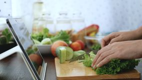 4K 切绿色菜的女性手,成份为烹调做准备通过片剂跟随烹调在网站上的网上录象剪辑 影视素材