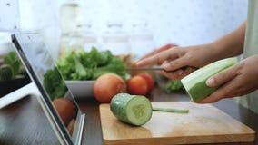 4K 切黄瓜果皮的女性手,成份为烹调做准备通过片剂跟随烹调在网站上的网上录象剪辑 股票录像